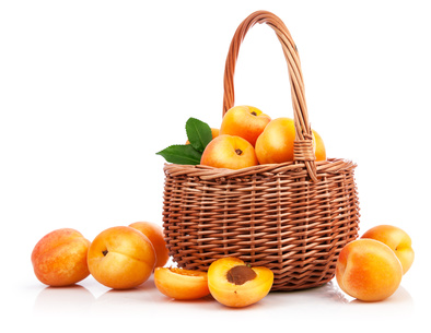 Fresh apricot with green leaf in wicker basket still life of fruits, isolated on white background and copyspace